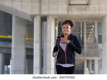 Portrait of a smiling young woman jogging outdoors