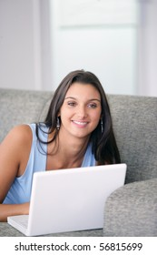 Portrait of a smiling young woman laid on a sofa in front of a laptop computer