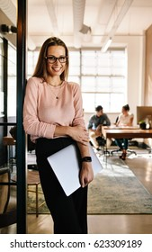 Portrait of smiling young woman leaning to office doorway holding laptop. Beautiful female executive at office with people working in background.