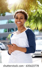 Portrait of smiling young woman listening to music with earphones and mobile phone