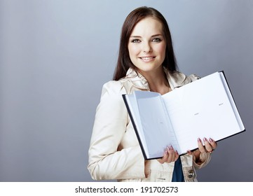 Portrait of a smiling young woman, with long brunette hair, on gray studio background, holding an open photobook or album in her hands