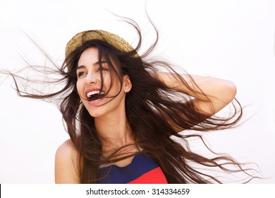 Portrait of a smiling young woman with long hair blowing in the wind