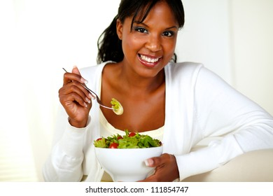 Portrait of a smiling young woman looking at you while enjoying a amazing green salad at light background.