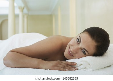 Portrait of smiling young woman lying on massage table at spa