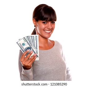 Portrait of a smiling young woman with money looking at you standing over white background