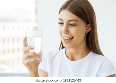 Portrait of smiling young woman with Omega 3 fish oil capsule