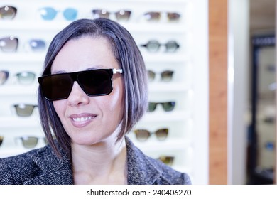portrait of a smiling young woman at optical shop wearing very fashionable sunglasses with the sunglasses expositor at background - focus on the glasses center