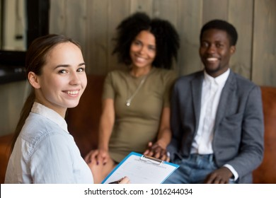 Portrait of smiling young woman professional psychologist or counselor looking at camera with happy african american couple at background, effective family therapy and marriage counseling concept