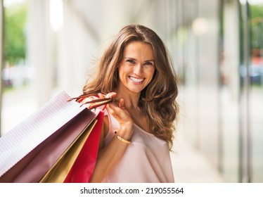Portrait of smiling young woman with shopping bags
