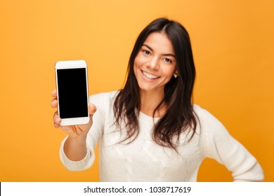 Portrait of a smiling young woman showing blank screen mobile phone isolated over yellow background