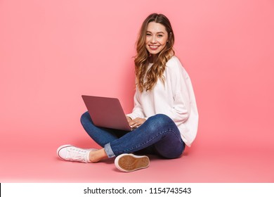 Portrait of a smiling young woman sitting with legs crossed, using laptop computer isolated over pink background