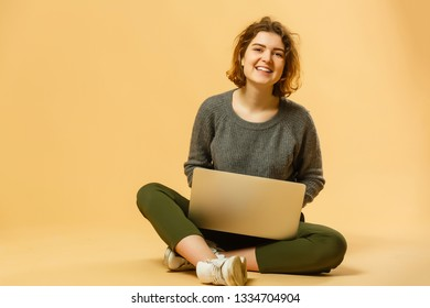 Portrait of a smiling young woman sitting with legs crossed, using laptop computer isolated over yellow background