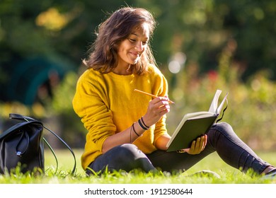 Portrait smiling young woman sitting on grass in park writing in book