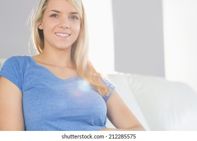 Portrait of a smiling young woman sitting on sofa in the living room at home