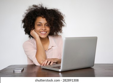 Portrait of a smiling young woman sitting at table with laptop