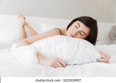 Portrait of a smiling young woman sleeping with a pillow on bed at the bedroom