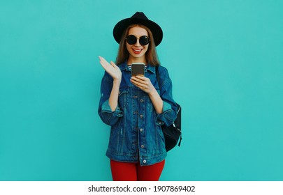 Portrait of smiling young woman with smartphone wearing a black round hat, denim jacket on a blue background