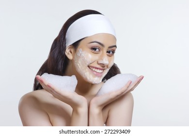 Portrait of smiling young woman with soap sud over white background