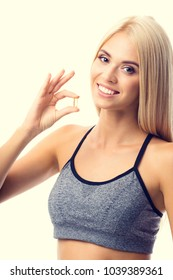 Portrait of smiling young woman in sportswear with Omega 3 fish oil capsule, indoors. Health care and medical concept with caucasian beautiful  blond model.