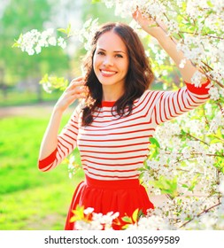 Portrait smiling young woman with spring flowers at garden