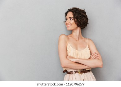 Portrait of a smiling young woman standing with arms folded and looking away at copyspace isolated over gray background