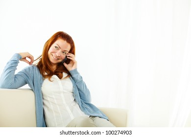 Portrait of a smiling young woman talking at cellphone
