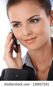 Portrait of smiling young woman talking on mobile phone.