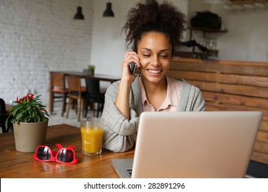 Portrait of a smiling young woman talking on mobile phone and working on laptop at home