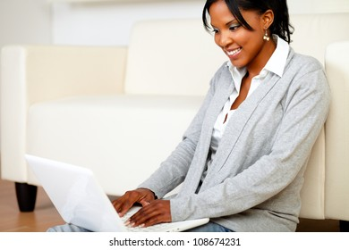 Portrait of a smiling young woman using laptop while is sitting on the floor