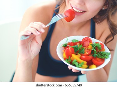 Portrait of smiling young woman with vegetarian vegetable salad