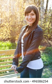Portrait of smiling young woman walking on the spring park in sun rays, standing next to bench