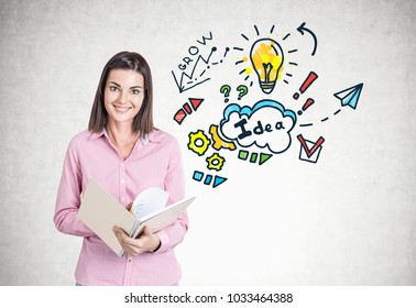 Portrait of a smiling young woman wearing a pink shirt and holding an open copybook. A concrete wall background with a good idea sketch.