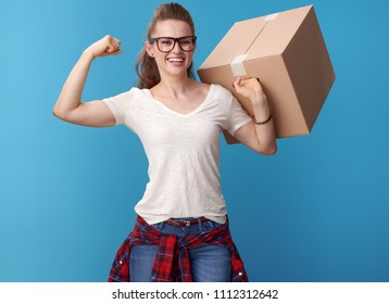 Portrait of smiling young woman in white shirt with a cardboard box showing biceps isolated on blue