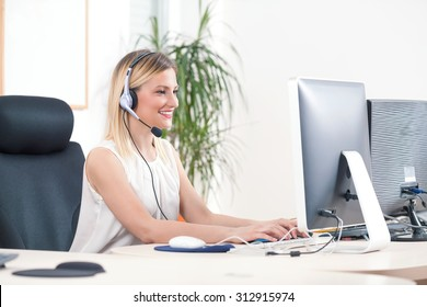 Portrait of smiling young woman working on a computer in a call center