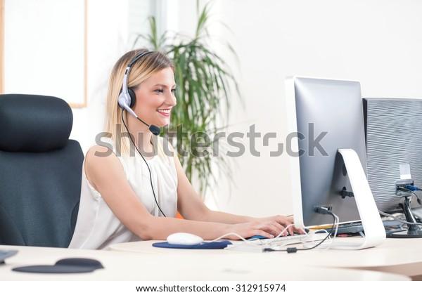 Porträt einer lächelnden jungen Frau, die in einem Callcenter an einem Computer arbeitet