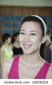 Portrait of smiling young woman in yoga studio