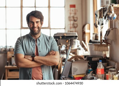 Portrait of a smiling young woodworker standing with his arms crossed by a workbench full of tools in his carpentry workshop