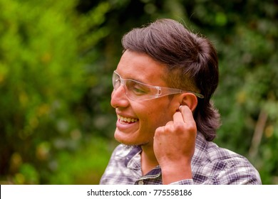 Portrait of smiling young worker wearing transparent safety glasses, and wearing a long sleeve shirt, putting ear plugs to protect from noise, in a blurred nature background