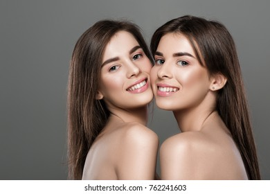 portrait of smilingl twins women with perfect skin and natural make-up and long hair. fashion