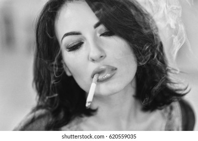 portrait of the smoking brunette with a cigarette, bad habit