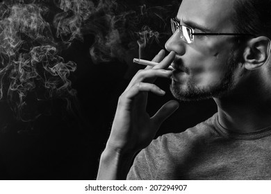 Portrait of smoking man with a cigarette in his hand on a dark background shot in studio