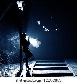 Portrait of a smoking woman in the style of noir. A middle-aged woman with a cigarette stands at night near a street lamp.