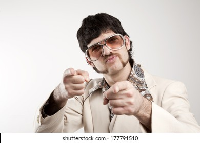 Portrait of a smug retro man in a 1970s leisure suit and sunglasses pointing to the camera
