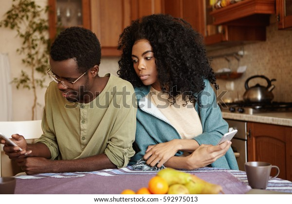 Portrait of sneaky and jealous young African wife spying on her husband, looking over shoulder, trying to see what he reading on his mobile phone. People, relationships and modern technology