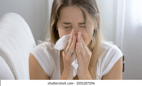Portrait of sneezing sick woman at home