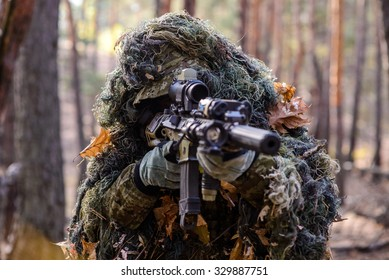 Portrait of sniper in the woods, which  aiming from his rifle/Sniper aiming from his rifle in forest