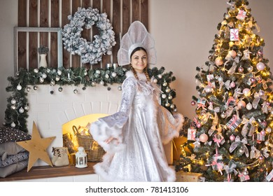 Portrait of a snow Maiden at the new years decorated Christmas tree.