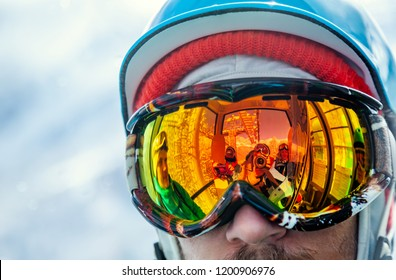 Portrait of snowboarder closeup in protective mask against the sun and reflection of friends, sitting inside cabin of cableway at winter resort. Reflection of the photographer