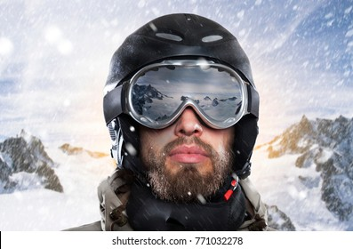 portrait of a snowboarder with helmet and goggles in front of sunrise in wintry mountains landscape while a stormy blizzard