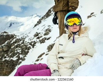 Portrait of snowboarder in helmet and protective mask on background of mountains